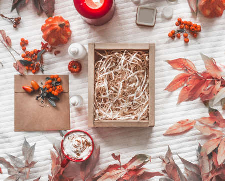 Product eco friendly packaging with empty cardboard boxes and wood chips surrounded by pumpkin, leaves, products, candle and wild berries. Hot chocolate with cream. White blanket background. Top view