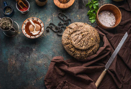 Homemade whole grain bread on dark kitchen table background with knife and cooking tools and ingredients. Top view. Place for text