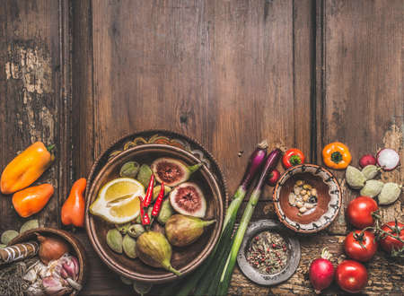 Healthy food and snack background. Bowls with tasty ingredients of Mediterranean cuisine: various vegetables, olives, pickled pepperoni and figs on wooden rustic table. Top view. Place for text Standard-Bild