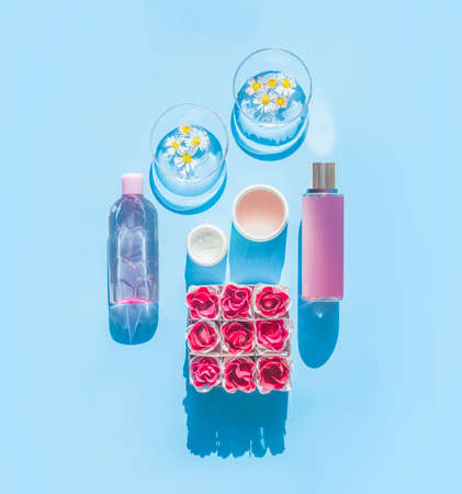 Composition of natural cosmetic products and glasses with daisies, bottles, tubes and flowers on light blue background. Summer skin care concept. Top view. Spa or wellness Standard-Bild