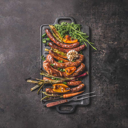 Grilled food on cast iron plate: sausage, pepper, spring onion, garlic, paprika, herbs, carrot with meet fork. Summer barbecue concept on dark table. Top view