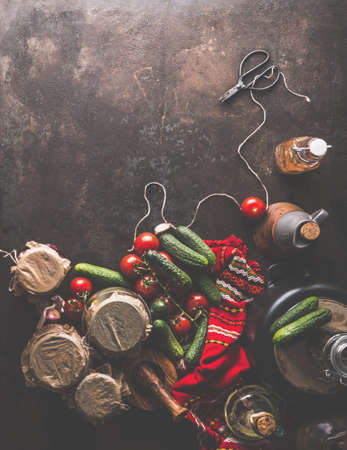 Preparation of homemade pickled cucumbers in jars with scissors, cord, red kitchen towel, oil, vegetables. Rustic autumn concept on dark background. Top view. Border Standard-Bild