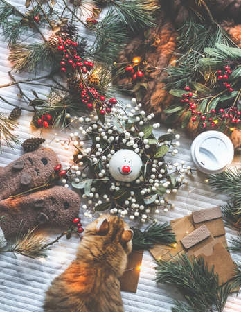 Christmas decoration: fir branches, winter berries, pine cone, cozy mood, fairy lights, paper gift packaging, gloves, coffee and cat around Christmas wreath with snowman. Textile background, top view