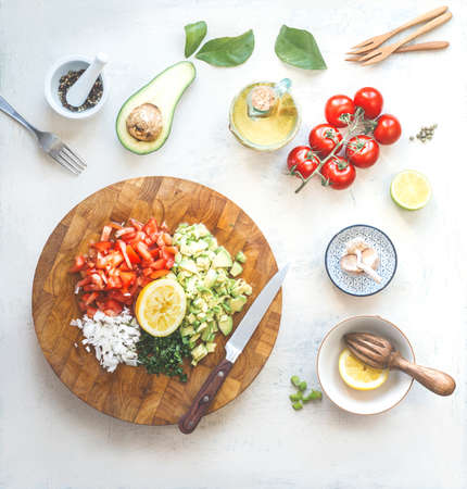 Chopped ingredients for avocado salsa, guacamole or salad on cutting board. Fresh cut avocado, tomatoes, lemon, lime, olives oil, garlic and chili a on white kitchen table. Top view