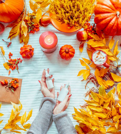 Women hands holding bottles of cosmetic products on white blanket with pumpkins, candles and fall leaves. Autumn beauty concept. Seasonal skin care. Flat lay. Top view