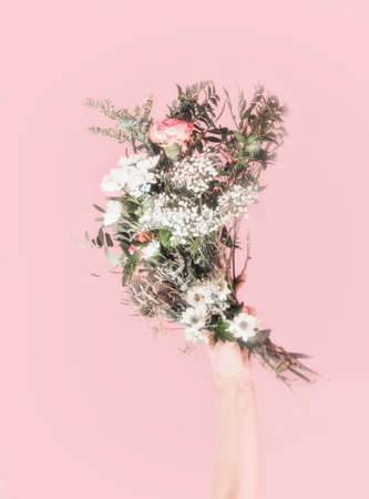 Women hand holding bouquet of fresh flowers at light pink background. Romantic concept. Front view. Pastel color