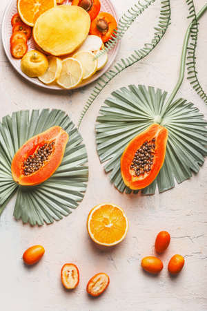 Sliced papaya with seeds on big, green leaves, various halves of orange and yellow fruits on light concrete background. Top view Standard-Bild