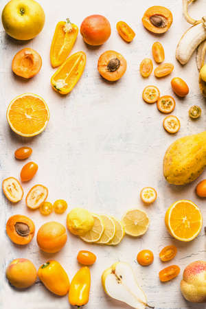 Frame of various yellow fruits and vegetables on white background. Top view. Halves of yellow fruits