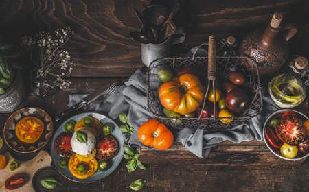 Rustic mediterranean food concept with fresh harvested colorful tomatoes and mozzarella. Homemade Caprese. Seasonal food on wooden background. Top view