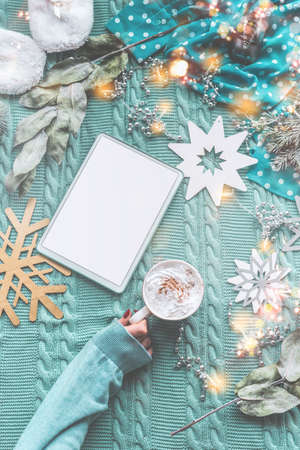 Woman hand in pullover holding cup of hot chocolate on blue knitted blanket with tablet and winter decoration. Winter holiday concept. Flat lay. Top view