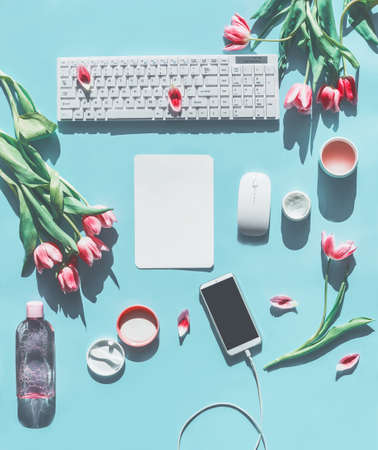 Spring concept with smartphone mock up, keyboard, tulips and natural cosmetic products on light blue background. Lifestyle beauty blogging concept. Flat lay. Top view