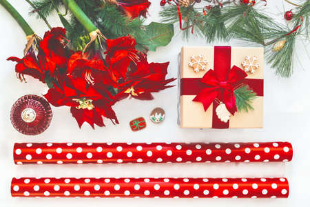 Christmas preparation: wrapping paper, gift, amaryllis and winter decoration. Christmas mood on white background. Top view Standard-Bild