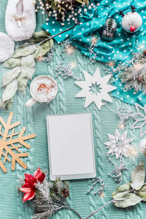 Christmas mood with tablet, cup of hot chocolate and snowflakes on blue textile background with decoration. Winter concept. Top view. Flat lay Standard-Bild