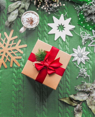 Christmas concept with gift and red ribbon, cup of hot chocolate and snowflakes on green knitted blanket background. Top view. Flat lay