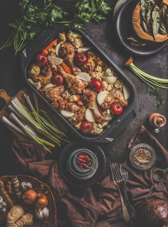 Fresh cooked food in baking dish with various ingredients, forks and kitchen equipment, kitchen cloth on dark concrete background, flat lay. Top view