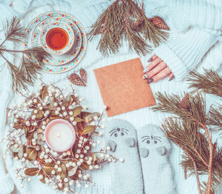 Winter and Christmas lifestyle flat lay. Women hand holding craft paper greeting card lies on white knitted blanket with fir branches, candles, cup of tea and cozy warm socks. Top view