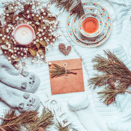 Winter and Christmas lifestyle flat lay. Craft paper greeting card lies on white knitted blanket with fir branches, candles, cup of tea and cozy warm socks. Top view Standard-Bild
