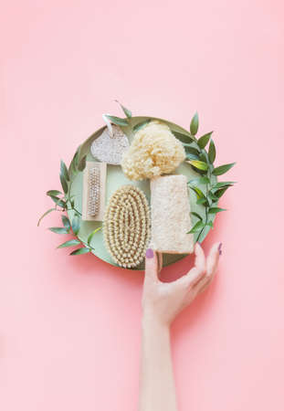 Women hand with eco friendly beauty and skin care bathroom accessories: natural sisal brush, wooden comb, soap, reusable make up removal pads. Zero waste. Top view. Natural and pastel colors.