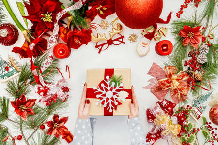 Women hand holding Christmas gift box on white desk with various Christmas decoration. Top view