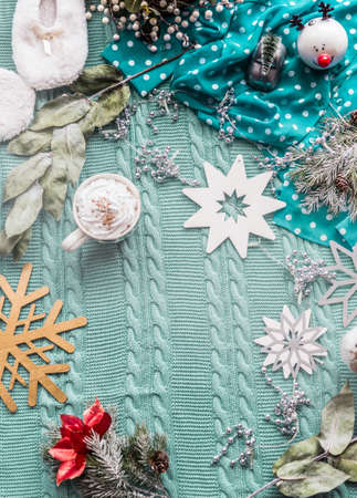 Winter lifestyle background with blue blanket, cup of cappuccino and various Christmas decoration. Top view. Frame