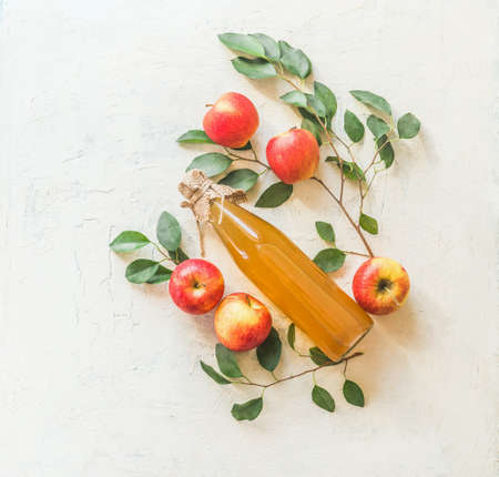 Composing with homemade apple juice in glass bottle with apples and green leaves on white background. Top view Zdjęcie Seryjne - 159358172
