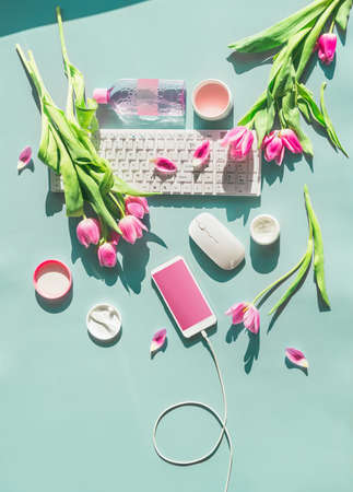 Female home office. Pastel blue desktop with PC keyboard, smartphone with blank screen and wire, cosmetics and pink tulips flowers in sunlight. Top view. Flat lay. Springtime. Blog layout
