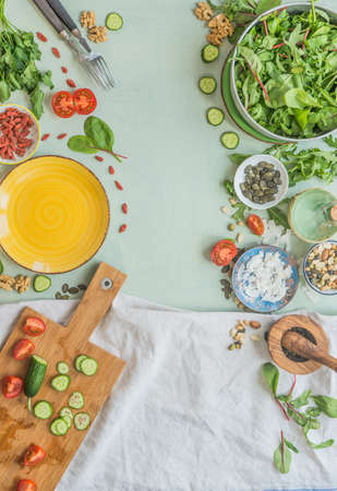 Various healthy salad ingredients on light green kitchen table background. Top view. Healthy lunch preparation, frame Standard-Bild