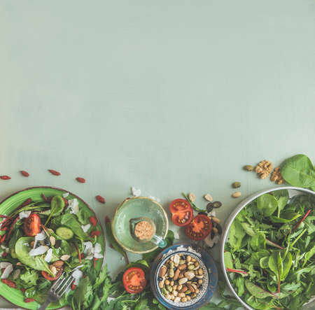 Green salad with nuts topping in plates on light green background with ingredients. Healthy lunch. Top view. Frame. Copy space Standard-Bild