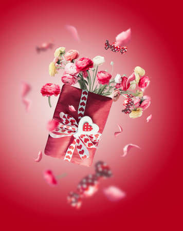Red flying gift box with flowers bunch, candies, heart and ribbon at red background. Valentines day. Greening with love.