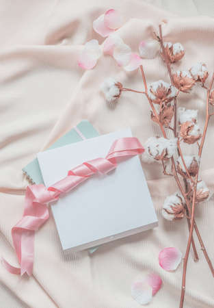 Aesthetic lifestyle with notebook, white box and pink ribbon on beige fabric background with cotton branches and pink petals. Top view. Beauty Standard-Bild
