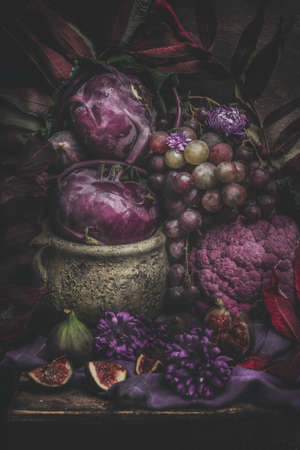Still life with purple fruits and vegetables. Dark