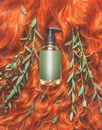 Red ginger hair with green leaves and cosmetic product bottle: shampoo, hair conditioner and care. Beauty and hair styling concept. Mock up Standard-Bild