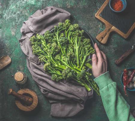 Women hand in green sweatshirt holding wild broccoli on dark rustic background. Top view. Healthy food