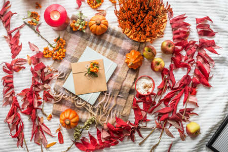 Cozy autumn lifestyle with pumpkins, red fall leaves, cappuccino, candles with notebook and envelope on white blanket. Top view. Flat lay Standard-Bild