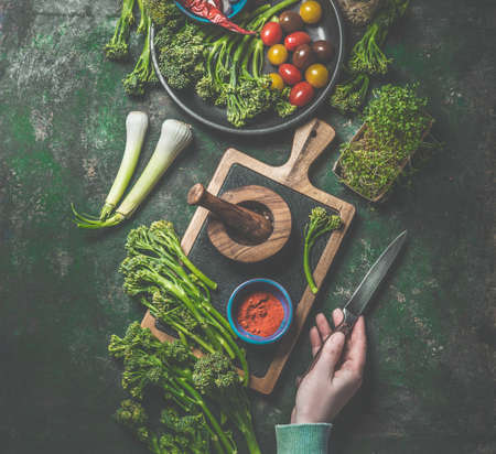 Cooking preparation of wild broccoli. Women hand holding knife on dark rustic background with cutting board and ingredients. Top view. Healthy food