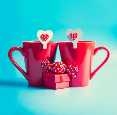 Two red mugs with hearts, candies and presents on blue background.