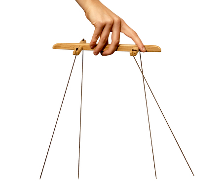 hand manipulating puppets strings on white background