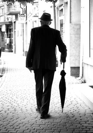 old man elderly man walking down the street with umbrella for rain