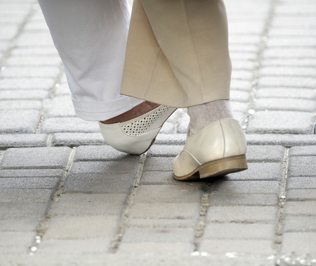 legs of old people dancing tango in white shoes