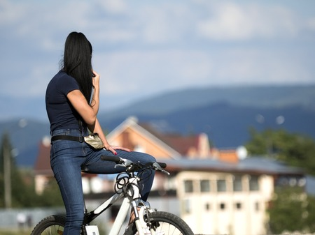girl on a bicycle in the city on a background of mountains