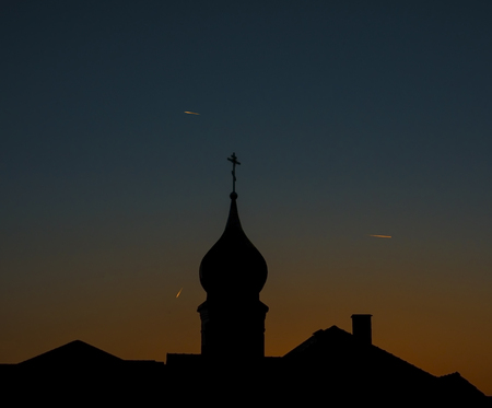 Black silhouette of a Christian temple against the evening sky