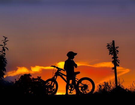 silhouette of a boy with a bicycle at sunset