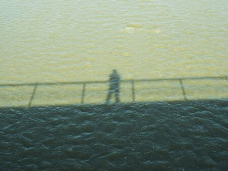 the shadow of the bridge on the water of the river