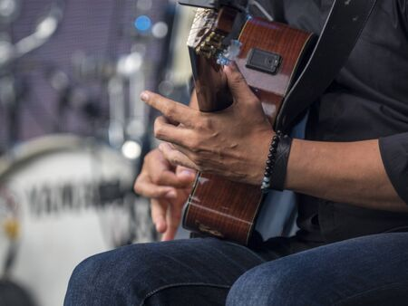 the hands of a guitarist playing the guitar