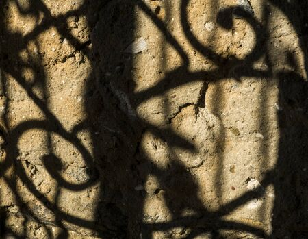shadow from a forged lattice on an old wall
