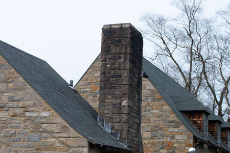 Tiled roof top with chimney stone fasade