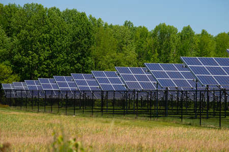 Modern solar panels on beautiful green grass with sun and clouds alternative energy concept outdoor