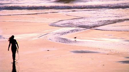 A female surfer walking towards ocean in Beacons Beach, Encinitas, California photo