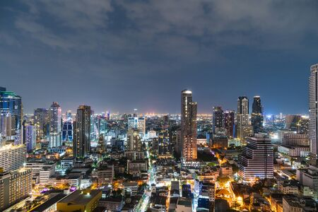 Cityscape of picturesque Bangkok at night time from rooftop. Panoramic evening skyline of the capital city of Thailand. The concept of metropolis.