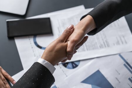 Top view of two businesswomen shaking hands at blurred office table with graphs. Concept of partnership and collaboration